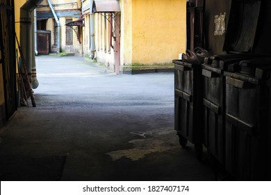 Narrow dark aisles in the old town, urban, grunge aged street. Arch and lane, garbage bins, old city