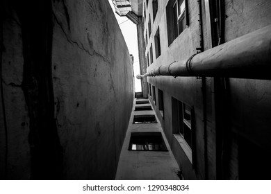 narrow deadlock with a drainpipe in the downtown of Saint Petersburg in black and white