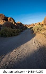 narrow desert dirt road thru rock formations of Alabama Hills, Sierra Nevada mountains, Lone Pine, California