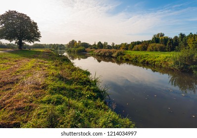 The narrow Dutch river Mark in the autumn season. The nature is already changing the colors. The photo was taken on a sunny morning near the village of Strijbeek in the province of Noord-Brabant.