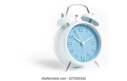 Narrow focus to clock with time 10 past 12 or 10.00 AM PM, blue clock face, on white background