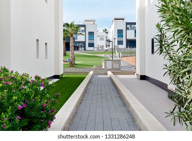 Narrow footpath along between two white residential houses path leading to green lawn inside of residential urbanisation Modern architecture similar townhouses in row, private area, summer landscape