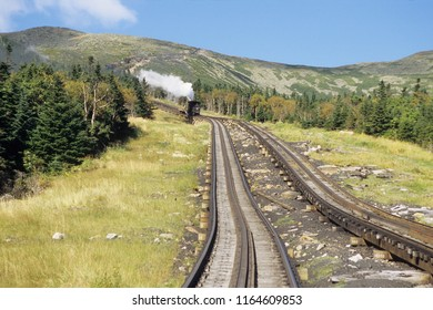 narrow gauge cog rail steam locomotiv is pushing up coach at Mount Washington summit during good weather conditions