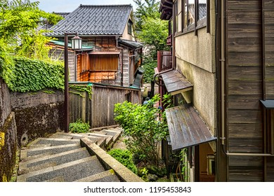 Narrow Historic Alley with Stone Steps in Historic Japanese City with Traditional Wooden Architecture, Slanted Roofs, and Greenery. Summer Day, No People (Kanazawa, Ishikawa Prefecture, Japan).