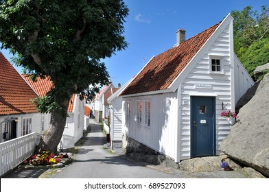 Narrow idyllic alley with white wooden houses in Skudeneshavn in southern Norway