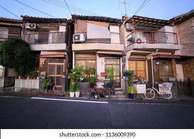 Narrow Japanese houses with mama cherry bicycles parked in typical quiet neighborhood