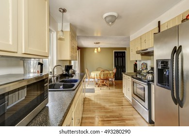 Narrow kitchen room interior with black and steel appliances, dark granite counter tops, beige cabinets and light tones hardwood floor. Northwest, USA
