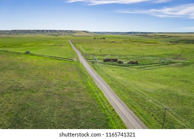 Narrow lane leads between the fields of a farm in the American west.