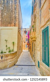 The narrow lane in nedieval Mdina fortress with historical edifices with external decorations, Malta