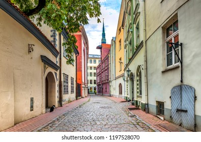 Narrow medieval street in old district of Riga - the capital city of Latvia and famous tourist center in Baltic region of Europe, EC