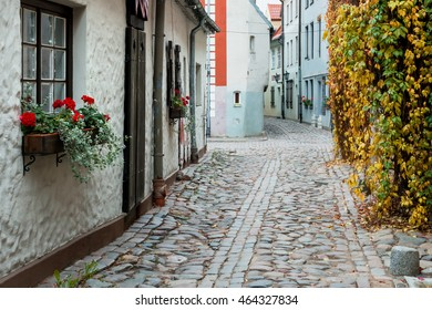Narrow medieval street. Walking through medieval streets of old Riga tourists can feel unforgettable atmosphere of the Middle Ages