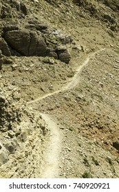 Narrow mountain path in summer. The path is heading downhill, following the mountain side.