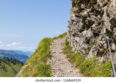 Narrow mountain path or trail in summer. The path is heading uphill, following the mountain side. Via Ferrata in the Stillachtal, Germany.