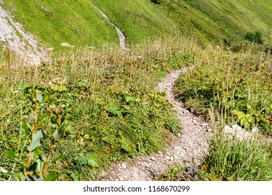 Narrow mountain path or trail in summer. The path is heading downhill, following the mountain side. Via Ferrata in the Stillachtal, Germany.