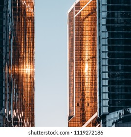 A narrow pass between two business office skyscrapers with stunning sun reflections on the teal and orange glass facades, with blue sky at the end of the passage