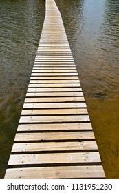 narrow plank footbridge over water with waves