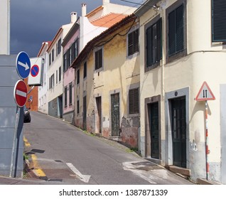 a narrow quiet empty street in funchal madeira with old painted houses on a steep hill with shutters and road signs n bright sunlight