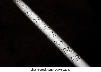 Narrow ray of light on a stone with inscriptions