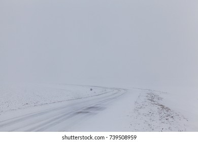 narrow road covered with snow. on the surface of the asphalt a few tracks, fog and snow in the distance, poor visibility. winter landscape