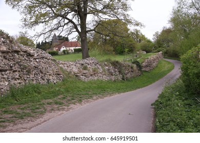 A narrow road winds around the perimeter of Silchester's (Calleva Atrebatum) magnificent Roman Wall. In the background can be seen the Norman-aged St Mary the Virgin Church