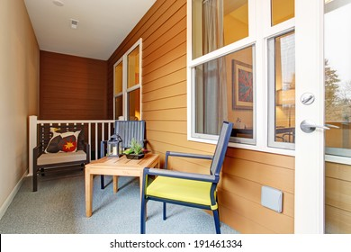 Narrow screened porch with wooden table and chairs