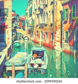 Narrow side canal with moored motorboats in Venice, Italy. Vintage style toned
