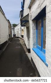 A narrow sidestreet in Polperro, Cornwall, with blue window frames