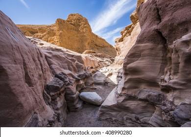 Narrow slot between two striped orange rocks in stone desert, Israel