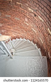 A narrow, spiral staircase leads down from the lighthouses light room deeper into its interior