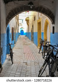 A narrow street, or alley, just off the main street is empty except for some bikes. This is in the souk of center of the old city of Essaouira, Morocco.