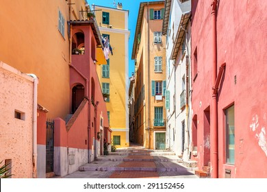 Narrow street among old colorful houses in Menton, France.