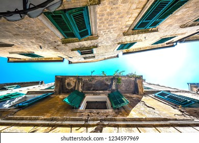 The narrow street of the ancient city, looking up at the open window with wooden shutters under a beautiful aged balcony, collapsing yellow wall with cracks. Kotor Old Town, Montenegro.