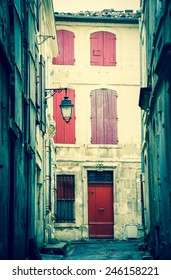 Narrow the street in Arles (Provence, France). Weathered stucco walls, red wooden shutters and forging lanterns. Aged photo.