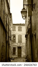 Narrow the street in Arles (Provence, France). Weathered stucco walls, red wooden shutters and forging lanterns. Aged photo. Sepia.