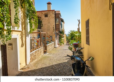 Narrow street with art shop and scooters of old town in City of Rhodes (Rhodes, Greece)