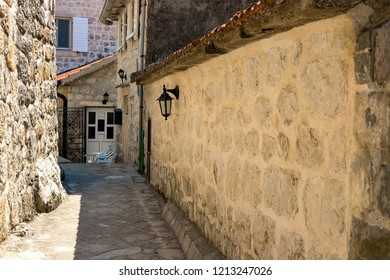 Narrow street of authentic old town Perast, Montenegro. We see old houses and a narrow street with a stone wall.