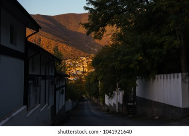 A narrow street in the background of high mountains during sunset