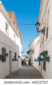 a narrow street with blue plant pots in mijas pueblo