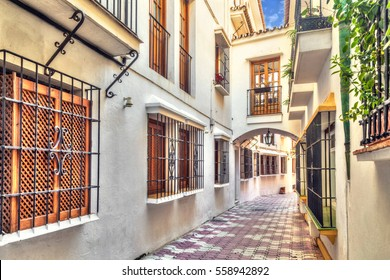 Narrow street with bridge between houses in old town of Marbella, Andalusia, Spain