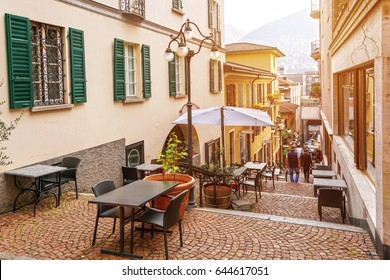 Narrow street with cafes and restaurants in the old town of Lugano, canton of Ticino, Switzerland.