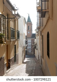 Narrow street with church, clock tower and balconies in Archidona, Andalusia, Spain