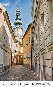 A narrow street of cobblestones leads towards the belltower of a church in the Old Town of Bratislava in Slovaka.