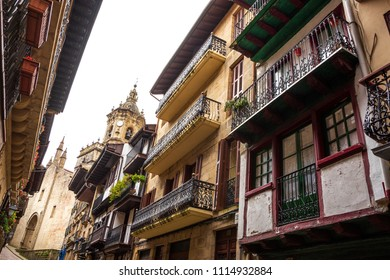 Narrow street of  Hondarribia with its colorful picturesque houses and Parish Church of Santa Maria de La Asuncion y del Manzano at background.