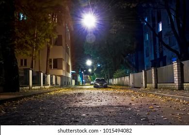 A narrow street at the Kadriorg area in Tallinn, Estonia. The autumn night is dark, but the area is illuminated with the street lights hanging on top of the street.