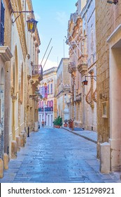 The narrow street leads along lines of old medieval stone edifices in Mdina fortress, Malta