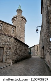 A narrow street leads past the exterior of the landmark Chateau de Virieu in the small town of Perussion, France.