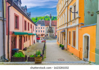 Narrow street of Loket town with colorful traditional typical buildings, street flowers and Column of the Holy Trinity at Marketplace square, Karlovy Vary Region, West Bohemia, Czech Republic