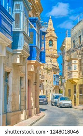 The narrow street with low historical edifices and Maltese balconies, Naxxar, Malta
