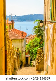 Narrow street in the Mediterranean city. Bright yellow houses in the Villefranche-sur-Mer, of the Cote d'Azur, France