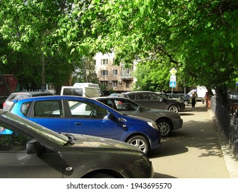Narrow street in Moscow, trees and cars
